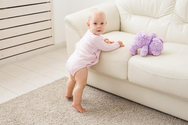Retrato de niña encantadora cerca del sofá