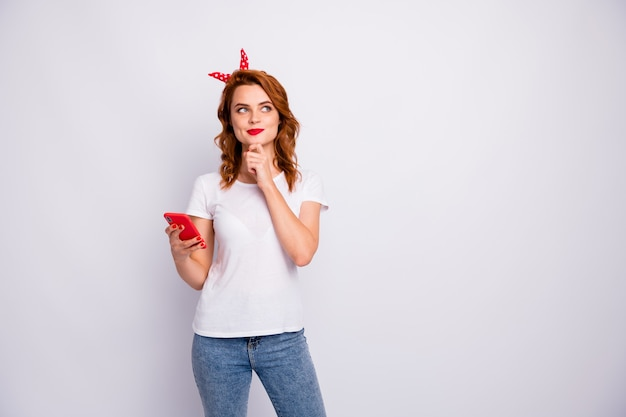 Retrato de niña encantadora interesada usar teléfono inteligente pensar pensamientos quieren blog publicación en redes sociales usar jeans camiseta aislada sobre pared de color blanco