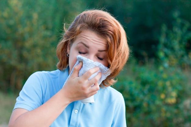 Retrato de niña enferma estornudando y soplando en una toallita al aire libre. mujer joven enferma que cubre la boca con una toallita. hembra con síntomas de alergia, resfriado, estornudos en los tejidos. fondo de verano