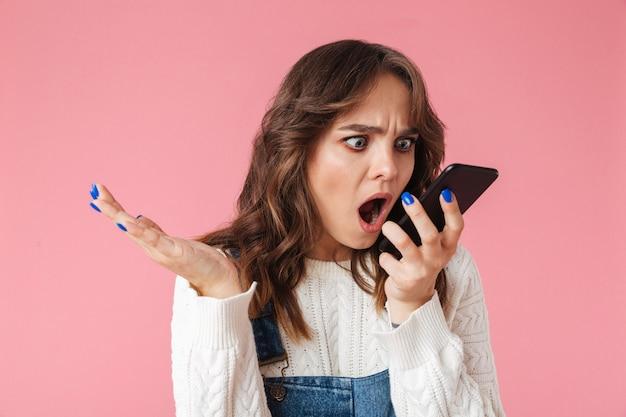 Retrato de una niña enojada gritando en el teléfono móvil