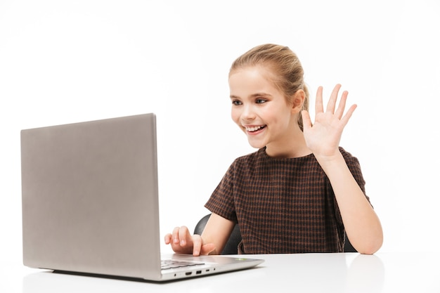 Retrato de niña de la escuela alegre regocijándose y usando la computadora portátil plateada mientras está sentado en el escritorio en clase aislado sobre la pared blanca