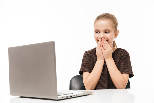 Retrato de niña de la escuela emocionada regocijándose y usando la computadora portátil plateada mientras está sentado en el escritorio en clase aislado sobre la pared blanca
