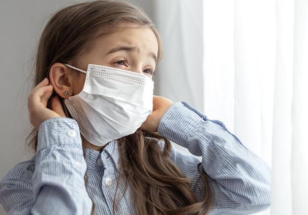 Retrato de una niña de la escuela primaria en una máscara protectora desechable. concepto de infancia durante pandemia y cuarentena.