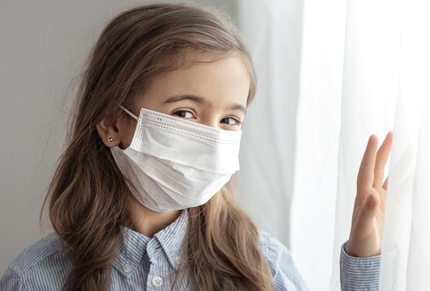 Retrato de una niña de la escuela primaria en una máscara protectora desechable