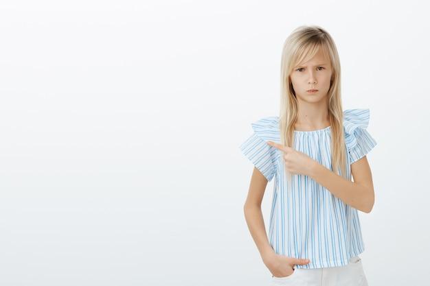 Retrato de niña europea enojada ofendida con cabello rubio, frunciendo el ceño y mirando por debajo de la frente, apuntando a la esquina superior izquierda mientras está de pie sobre la pared gris molesta