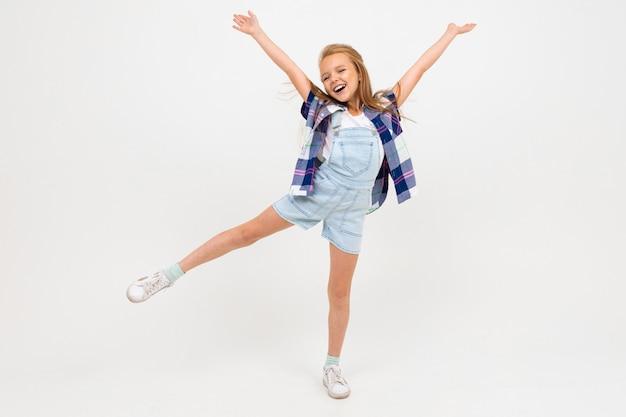 Retrato de niña europea feliz agitando las manos en blanco