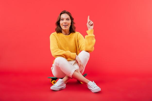 Retrato de una niña excitada sentada en una patineta