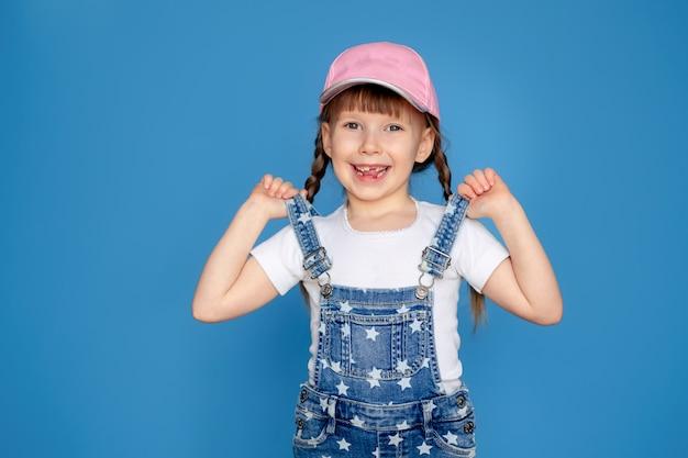 Retrato de una niña feliz 5-6 años de edad con una gorra, en una pared azul aislado, lugar para el texto. bebé desdentado. proteccion solar.