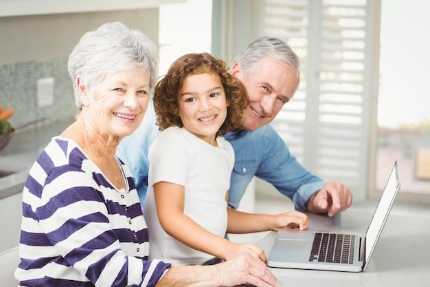 Retrato de niña feliz con abuelos usando laptop
