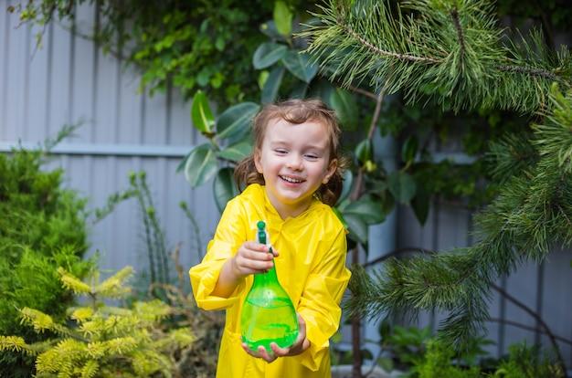 Retrato de una niña feliz ayudando a rociar plantas coníferas en un invernadero