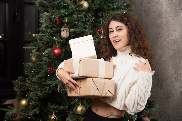 Retrato de niña feliz con cabello rizado sosteniendo una pila de regalos en un envoltorio