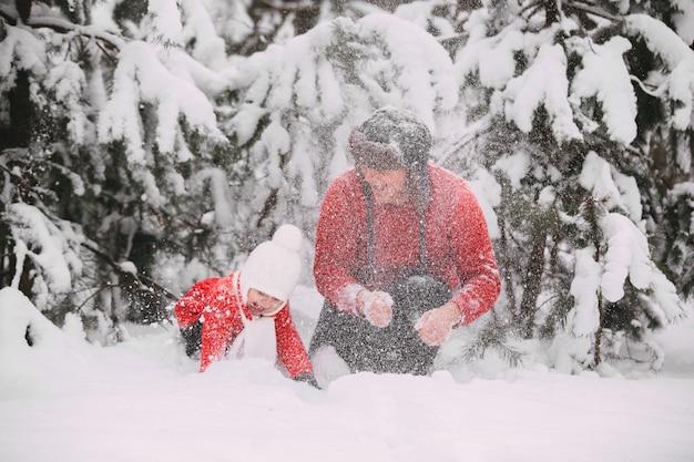 Retrato de niña feliz en capa roja con papá divirtiéndose con nieve en bosque de invierno. niña jugando con papá.