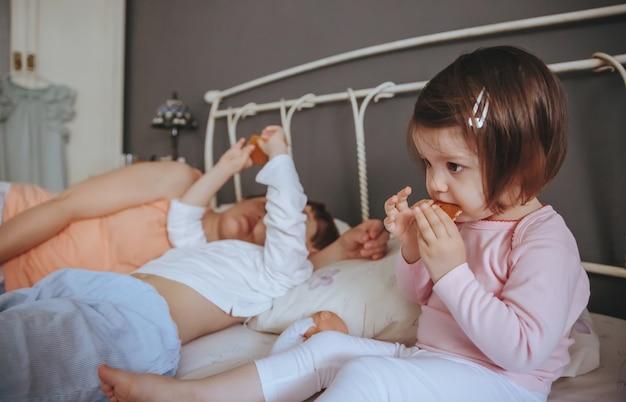Retrato de niña feliz comiendo galletas en la cama con su familia en una mañana relajada. concepto de tiempo de ocio familiar de fin de semana.