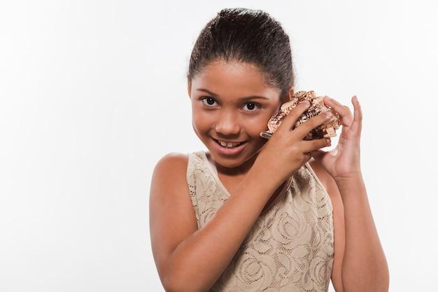 Retrato de una niña feliz con concha de mar
