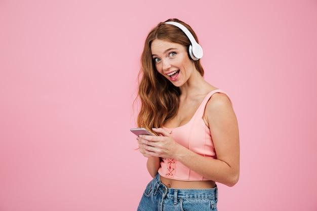 Retrato de una niña feliz emocionada en ropa de verano escuchando música