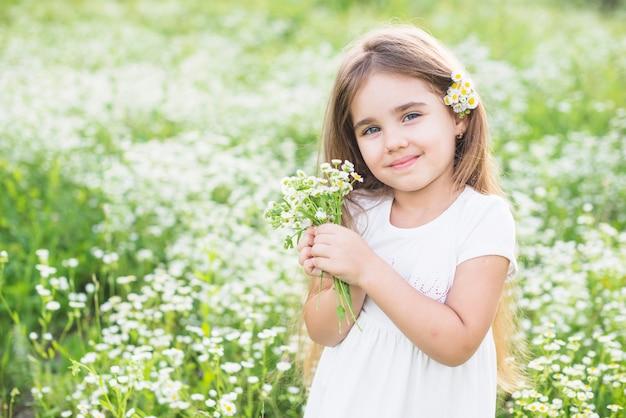 Retrato de niña feliz con flores blancas en la mano