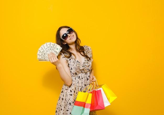 Retrato de una niña feliz con gafas de sol que muestra un montón de billetes mientras dinero y gesto de pie y sosteniendo bolsas de la compra