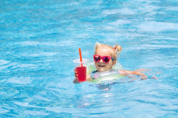 Retrato de la niña feliz linda que se divierte en piscina y que sostiene el jugo de la sandía de la mano