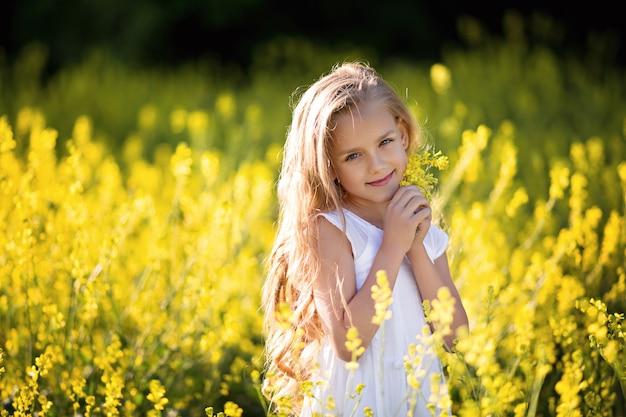 Retrato de una niña feliz en la naturaleza, en verano en un campo de violación.