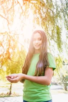 Retrato de una niña feliz de pie bajo el árbol en la luz del sol