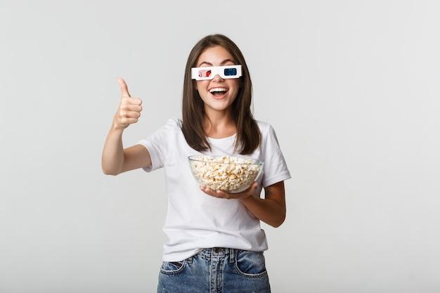 Retrato de niña feliz satisfecha en gafas 3d, sosteniendo un tazón con palomitas de maíz y mostrando el pulgar hacia arriba, como una gran serie de televisión o una película.