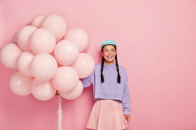Retrato de niña feliz satisfecha con largas trenzas, viste suéter suelto, falda, tiene un mínimo de maquillaje, se para con globos inflados contra la pared rosa