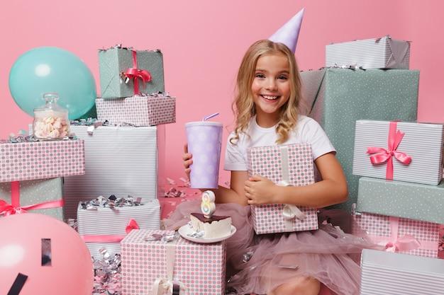 Retrato de una niña feliz en un sombrero de cumpleaños celebrando