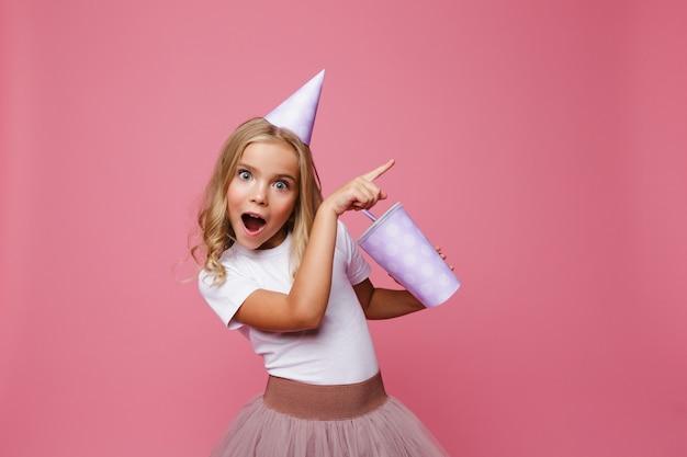 Retrato de una niña feliz en un sombrero de cumpleaños