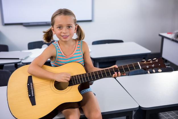 Retrato de niña feliz tocando la guitarra en el aula