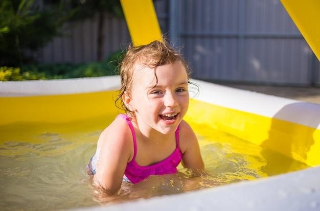 Retrato de una niña feliz en traje de baño flotando en una piscina inflable
