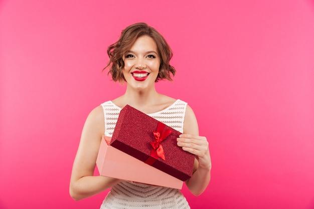 Retrato de una niña feliz vestida con vestido con caja de regalo