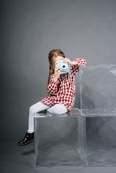 Retrato de una niña fotografiando a través de una cámara instantánea sentada en cubos transparentes sobre un fondo gris