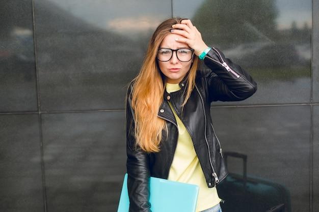 Retrato de niña con gafas negras y pelo largo de pie afuera sobre fondo negro. viste suéter amarillo y chaqueta negra. parece asustada y perdida.