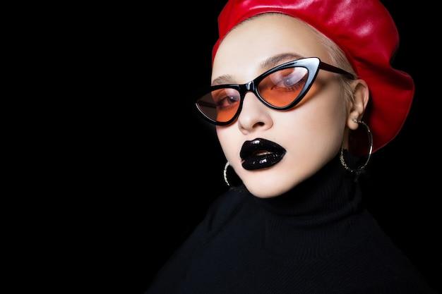 Retrato de una niña en gafas de sol con lápiz labial negro en los labios