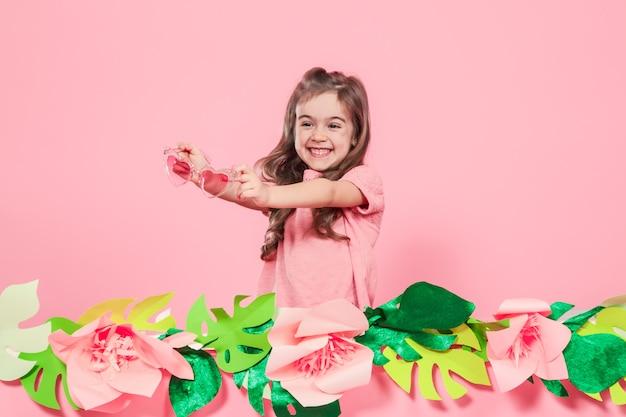 Retrato de una niña con gafas de sol sobre un fondo rosa