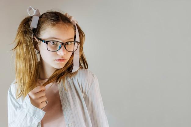 Retrato de una niña en gafas sosteniendo su cabello