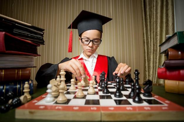 Retrato de niña genio en gorro de graduación jugando al ajedrez con ella misma