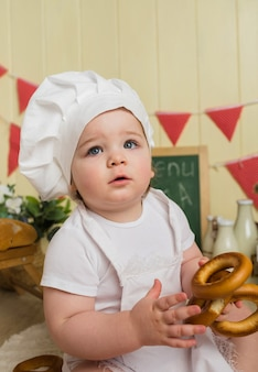Retrato de una niña con un gorro de cocinero sosteniendo un bagel