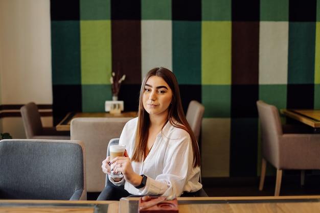 Retrato de niña hermosa, bebiendo té o café caliente en un café con su teléfono celular.