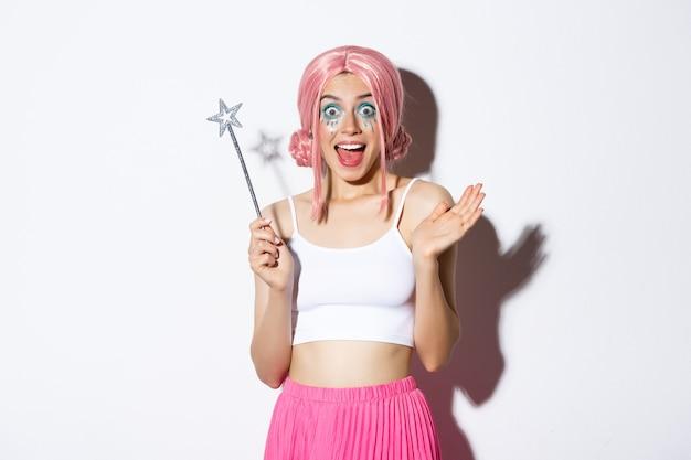 Retrato de niña hermosa glamour celebrando halloween con peluca rosa y traje de hada, sosteniendo magia y sonriendo feliz a la cámara, de pie