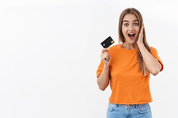 Retrato de niña hermosa rubia emocionada feliz, sorprendida le gusta ir de compras en línea