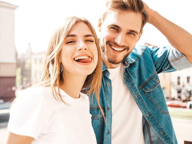 Retrato de niña hermosa sonriente y su novio guapo. mujer en ropa casual jeans de verano. . muestra lengua