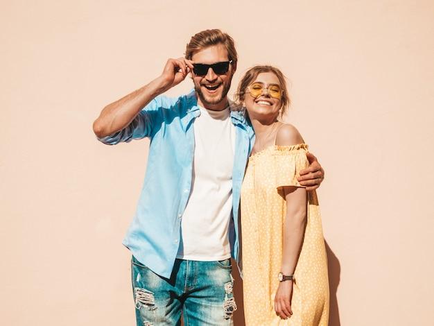 Retrato de niña hermosa sonriente y su novio guapo. mujer en vestido casual de verano y hombre en jeans. feliz familia alegre. mujer divirtiéndose en la calle cerca de la pared