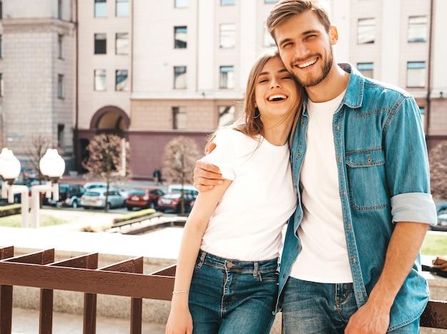 Retrato de niña hermosa sonriente y su novio guapo en ropa casual de verano. . abrazando