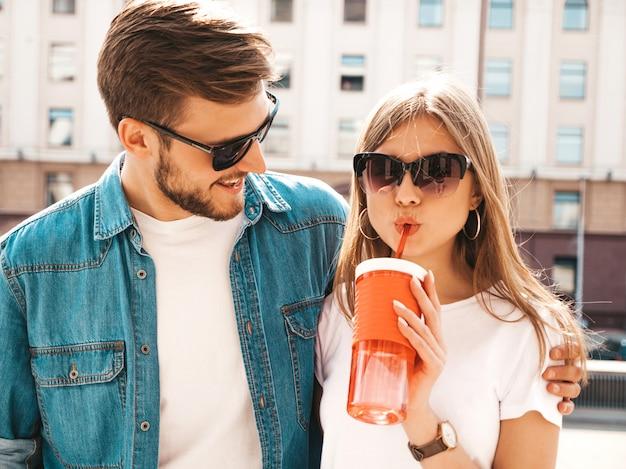 Retrato de niña hermosa sonriente y su novio guapo en ropa casual de verano. . con botella de agua y paja