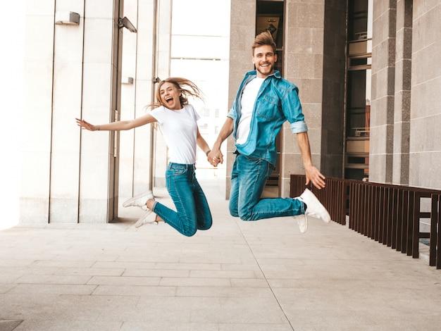 Retrato de niña hermosa sonriente y su novio guapo en ropa casual de verano. familia alegre feliz saltando y divirtiéndose en el fondo de la calle. volviéndose loco