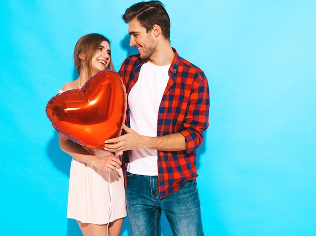 Retrato de niña hermosa sonriente y su novio guapo sosteniendo globos en forma de corazón y riendo. feliz pareja de enamorados. feliz día de san valentín. posando