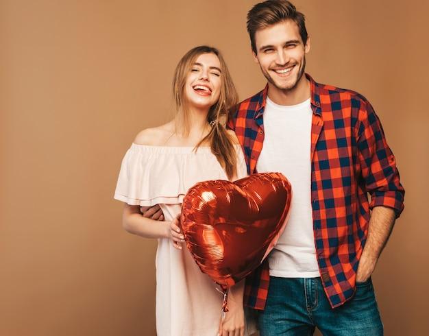 Retrato de niña hermosa sonriente y su novio guapo sosteniendo globos en forma de corazón y riendo. feliz pareja de enamorados. feliz día de san valentín