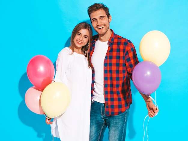 Retrato de niña hermosa sonriente y su novio guapo sosteniendo un montón de globos de colores y riendo. feliz cumpleaños
