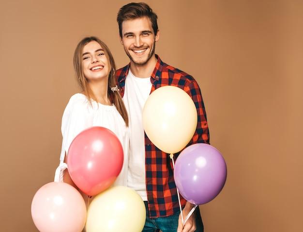 Retrato de niña hermosa sonriente y su novio guapo sosteniendo un montón de globos de colores y riendo. feliz pareja de enamorados. feliz cumpleaños